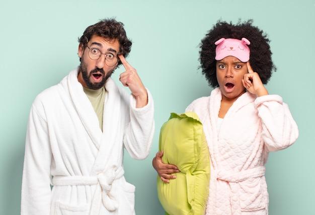 驚いた、口を開いた、ショックを受けた、新しい考え、アイデア、または概念を実現しているように見える多民族の友人のカップル。パジャマと家のコンセプト