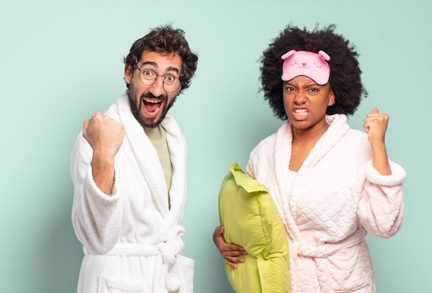 怒りの表情や成功を祝う拳で積極的に叫ぶ多民族の友人のカップル。