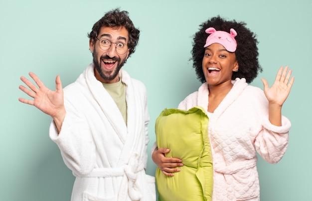 Многонациональная пара друзей счастливо и весело улыбаются, машут рукой, приветствуют и приветствуют вас или прощаются. пижамы и домашняя концепция