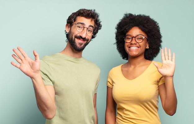 楽しく元気に笑ったり、手を振ったり、歓迎して挨拶したり、さようならを言ったりする多民族の友人のカップル