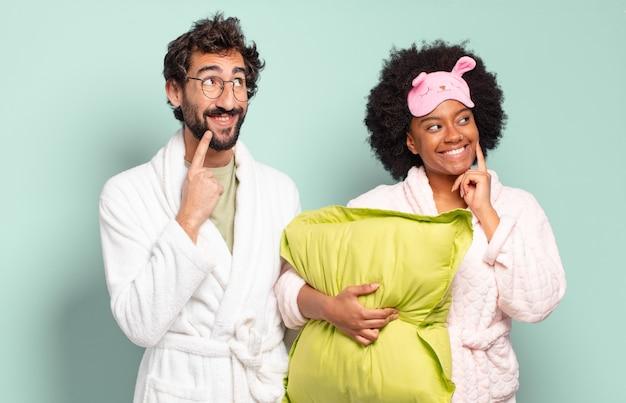 幸せに笑って、空想にふけったり、疑ったり、横を向いている多民族の友人のカップル。パジャマと家のコンセプト