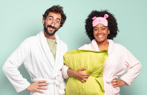 腰に手を当てて幸せそうに笑っている多民族の友人のカップル、自信を持って、前向きで、誇りに思って、フレンドリーな態度。パジャマと家のコンセプト
