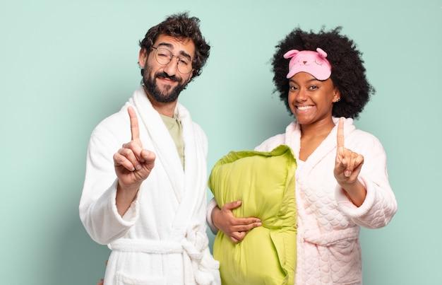 Многонациональная пара друзей, гордо и уверенно улыбающихся, торжествующе позируют номер один, чувствуя себя лидером. пижамы и домашняя концепция