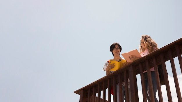 Multiracial couple reading books near wooden fence