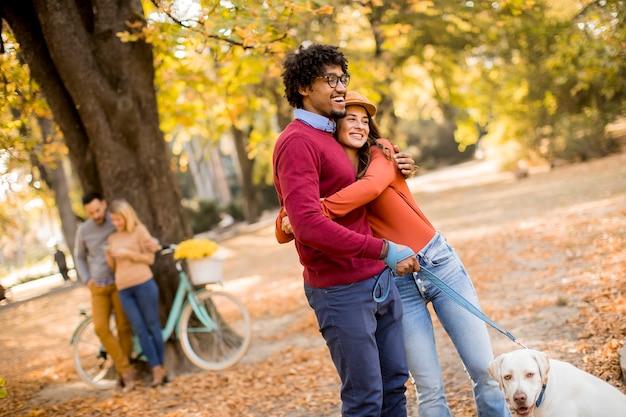 Многорасовая пара гуляет с собакой в желтом осеннем парке