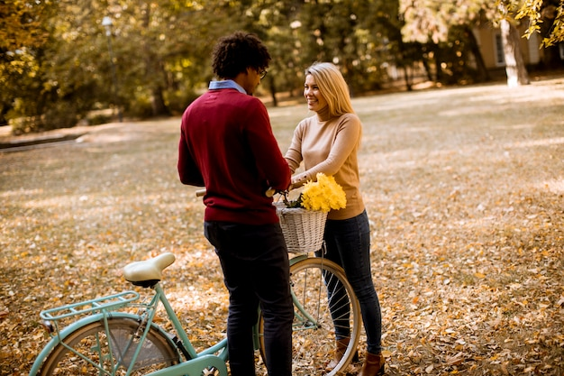 Multiracial couple with bicycle standing in the autumn park