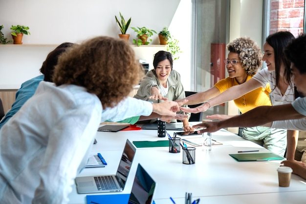 Multiracial coworkers join hands to celebrate teamwork success business teamwork celebration