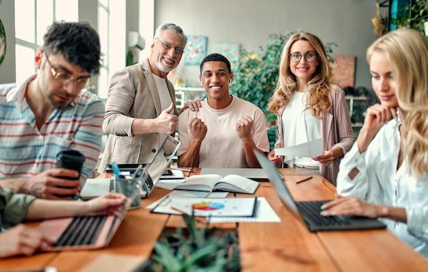 Многорасовые творческие люди в современном офисе. группа молодых деловых людей и старший босс работают вместе с ноутбуком, планшетом, смартфоном, ноутбуком, графиками. успешная команда в коворкинге