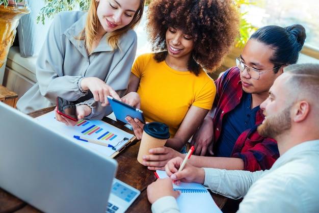Коллеги из разных рас, использующих планшет в творческом офисе