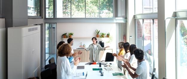 多民族の従業員が素晴らしい結果の後に女性の上司をたたくコピースペースバナービジネスのお祝い