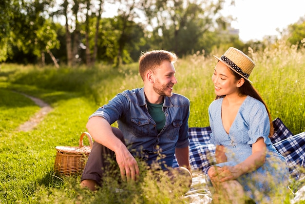 Multiracial enamored couple sitting on checkered plaid on grassy meadow