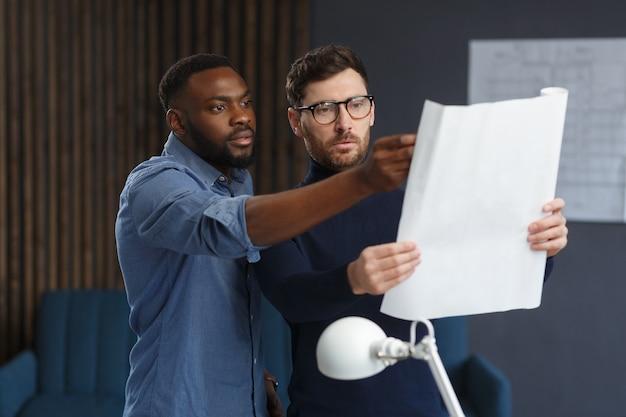Многорасовая команда инженеров, работающая в офисе с чертежами и эскизами оборудования для архитекторов, ...