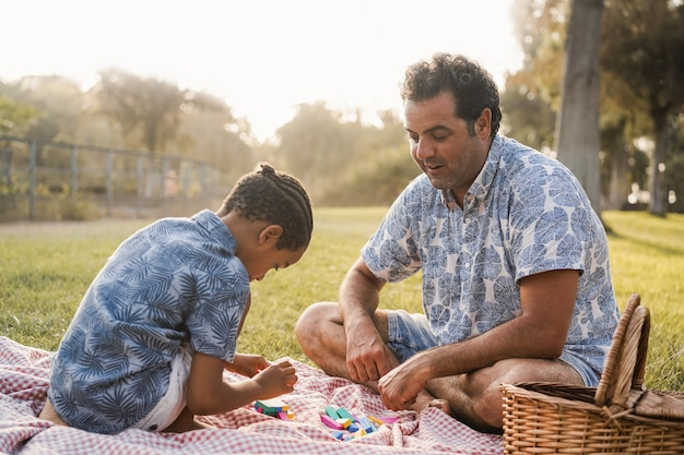 Multiracial father and son having fun with wood toys outdoor at city park - focus on dad face