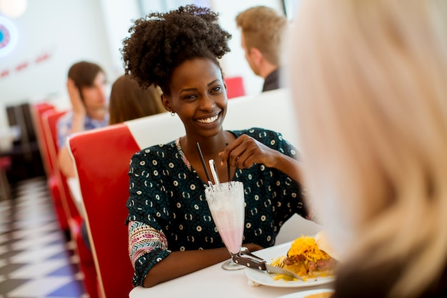 Multiracial female friends eating fast food at a table in the diner