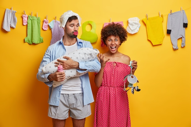 Multiracial friendly family care about newborn. father, mother and infant pose at home feed and play with baby, angry emotional mom holds mobile affectionate dad soothes little child