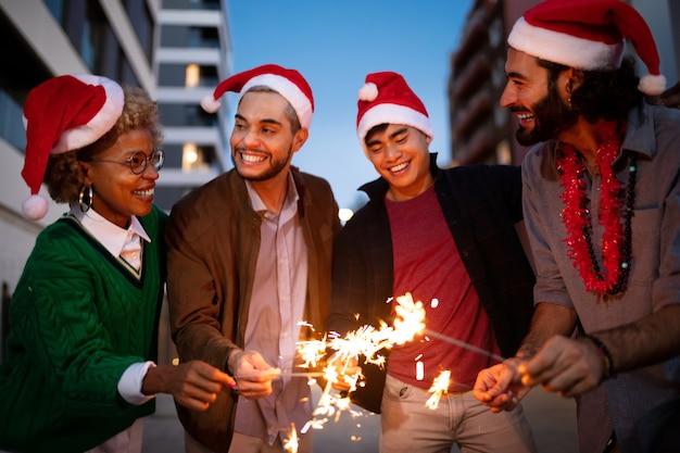 다인종 친구들은 산타클로스 모자를 쓰고 있는 폭죽과 함께 크리스마스를 축하합니다.