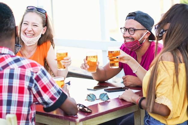 ビールで応援し、お互いに笑って笑っている多民族の友人-コロナウイルス/フェイスマスクのコンセプト