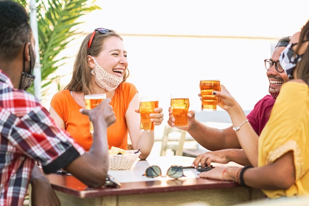 Multiracial friends cheering with beer and smiling laughing with each other - coronavirus/face mask concept