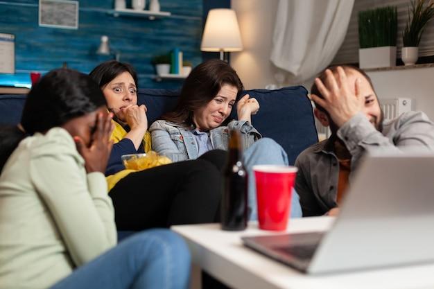 다인종 친구들은 밤 시리즈 동안 공포 스릴러 영화를 보면서 텔레비전 앞에 앉아 소파에 앉아 놀고 있습니다. 감정에 비명을 지르는 무서운 반응을 보이는 다민족 사람들.