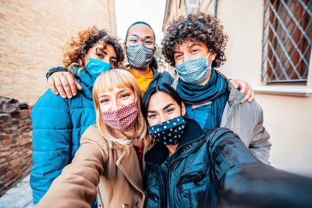 Multiracial friends covered by face mask taking selfie wearing winter clothes