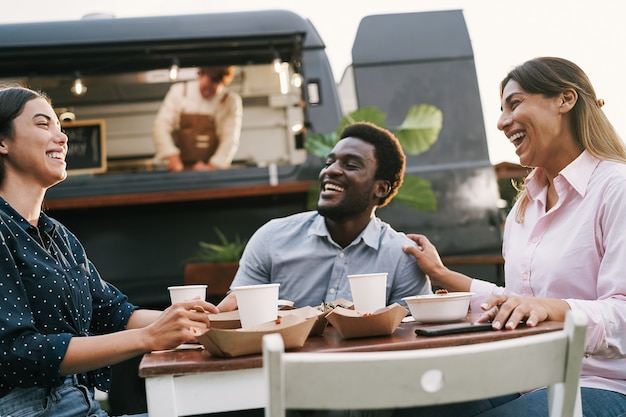 Multiracial friends eating at food truck table outdoor - summer and lifestyle concept - main focus on right woman face