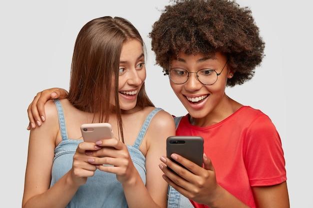 Gli amici multirazziali abbracciano e condividono file multimediali tramite il bluetooth del cellulare