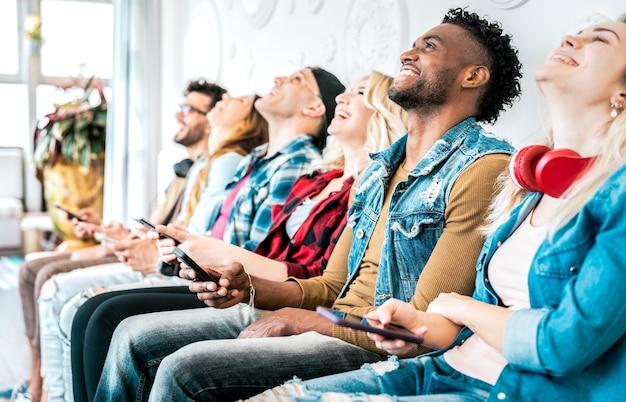 スマートフォンでビデオコンテンツを共有する多民族の友人グループ-ソーシャルネットでのインフルエンサーマーケティングのトレンドに携帯電話を使用している人々-常に接続されているミレニアル世代のテクノロジーコンセプト