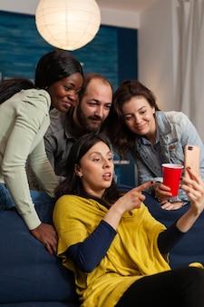 Друзья из разных рас тусуются поздно ночью и смотрят забавное развлекательное видео на смартфоне. группа многорасовых людей, проводящих время вместе, сидя на диване поздно ночью в гостиной.