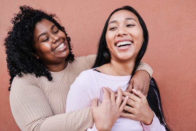 야외에서 즐겁게 껴안고 있는 다인종 친구 - 오른쪽 소녀에 초점