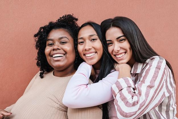 Многорасовые друзья веселятся вместе на свежем воздухе - сосредоточьтесь на лицах