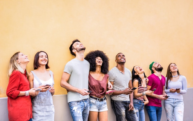 Multiracial friends having fun using smartphone at wall on university college break - young people addicted by mobile smart phones - technology concept with always connected millennials