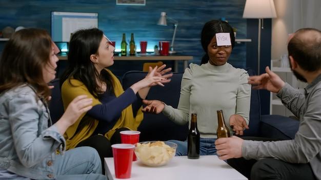 스티커 메모 그룹을 사용하여 함께 보드 게임을 하는 동안 웃고 있는 다인종 친구 하...