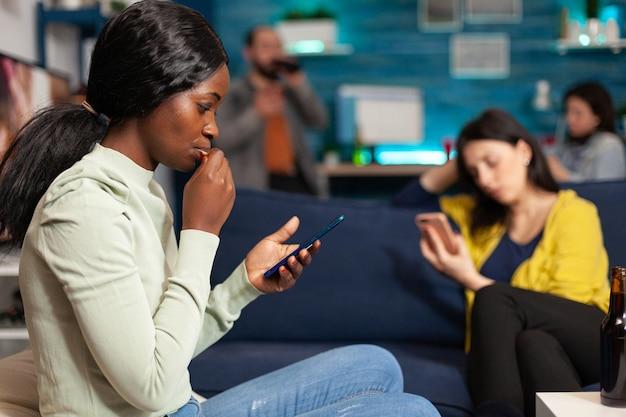 다인종 친구들은 깜짝 파티 중에 함께 모바일 과속 시간을 사용하여 인터넷에서 뉴스를 서핑하는 동안 소파에서 휴식을 취합니다. 거실에서 재미있는 온라인 영화를 보는 다민족 사람들의 그룹