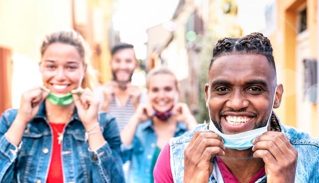 Многорасовые друзья улыбаются с открытой маской после открытия блокировки