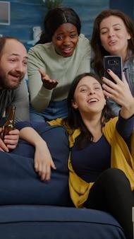 Многорасовые друзья разговаривают с коллегой во время видеоконференции с использованием современного смартфона
