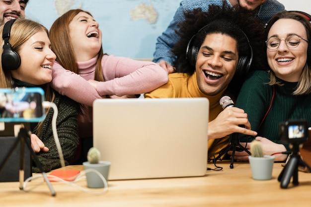 휴대 전화와 노트북 컴퓨터를 사용하여 온라인으로 스트리밍하는 다인종 친구 - 아프리카 남자 얼굴에 대한 주요 초점