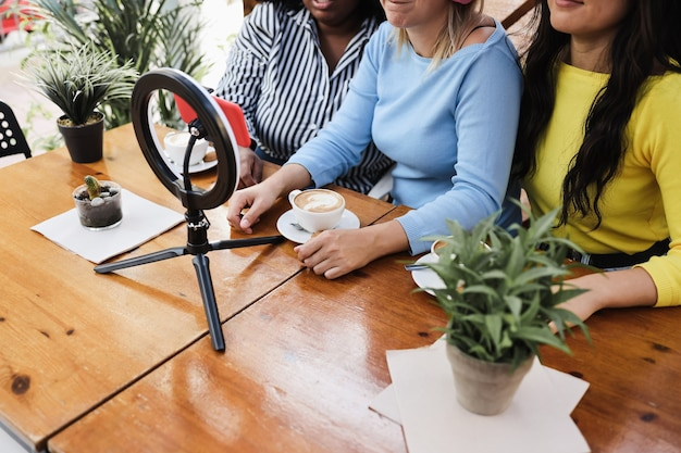 레스토랑에서 야외에서 휴대전화 카메라로 온라인 스트리밍을 하는 다인종 친구 - 센터 여성의 손에 초점