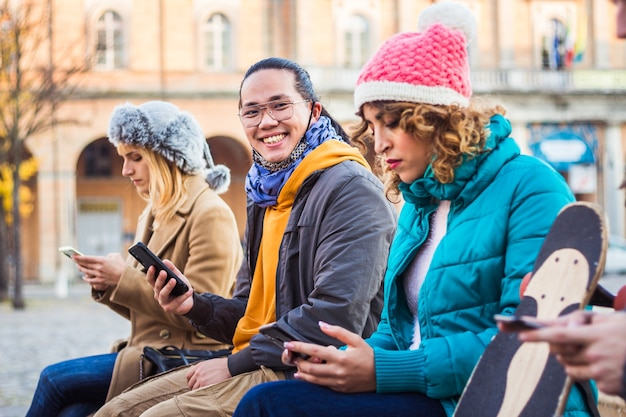 携帯電話追跡コロナウイルススプレッドを使用している多民族の友人