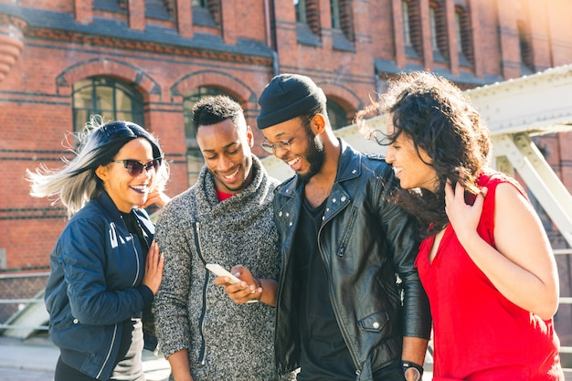 Multiracial friends using a smartphone and smiling