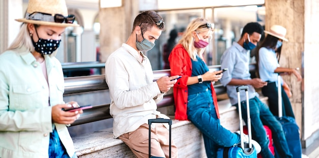 Multiracial friends wearing face mask using mobile smart phones - focus on first guy on the left