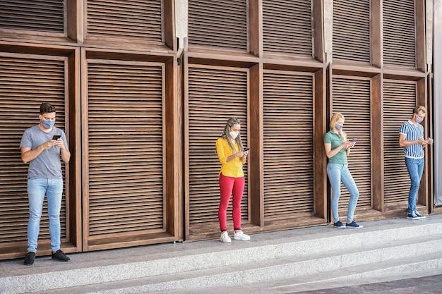 屋外で携帯電話を使用しながら保護フェイスマスクを着用している多民族の友人-社会的距離の概念