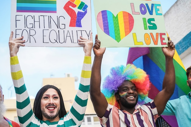 Multiracial gay people marching at lgbt pride parade with banners - focus on drag queen