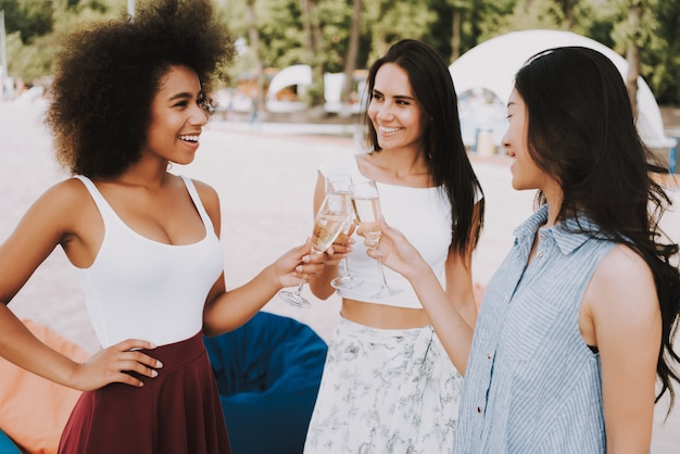 Multiracial girls clink glasses at beach party
