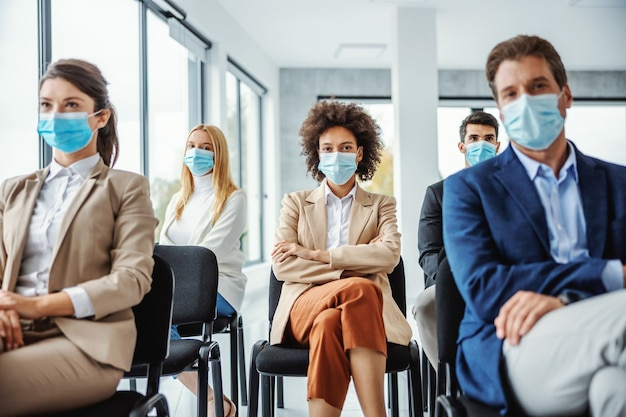 Multiracial group of business people with face masks sitting on seminar during corona virus