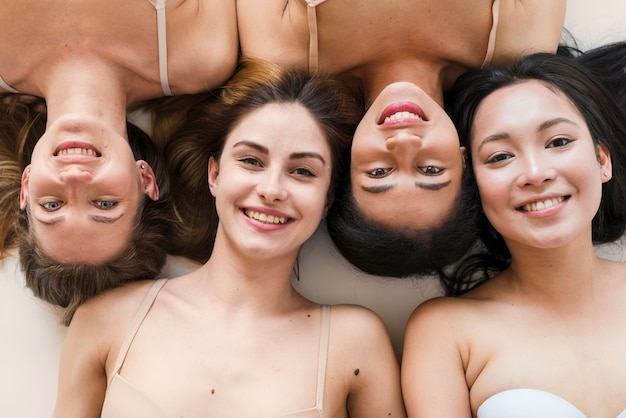 Multiracial group of cheerful young women lying on back
