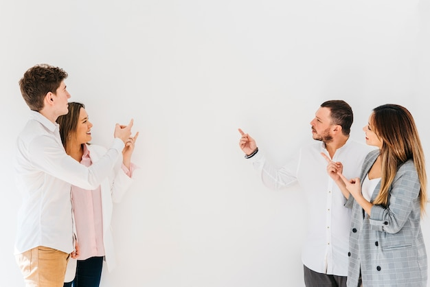 Multiracial group of coworkers pointing at wall