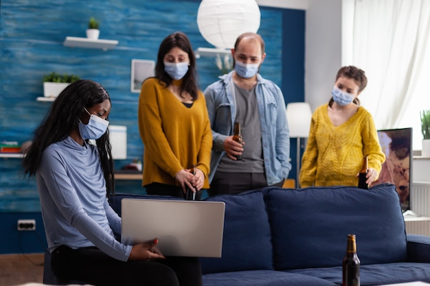 Multiracial group of friends chatting using laptop keeping social distancing and wearing face mask to prevent covid spread and infection in apartment living room. conceptual image