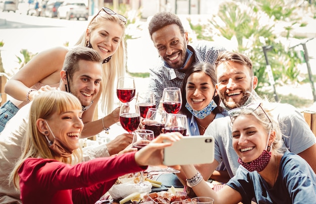 Multiracial group of friends wearing protection mask at the restaurant. happy people celebrating toasting red wine taking a selfie with smartphone.
