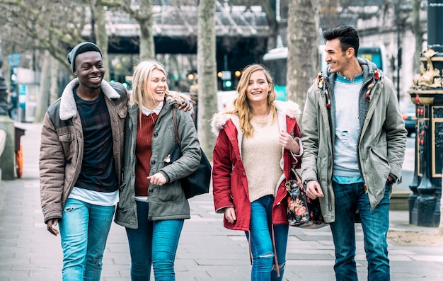 Multiracial group of millenial friends walking at london city center