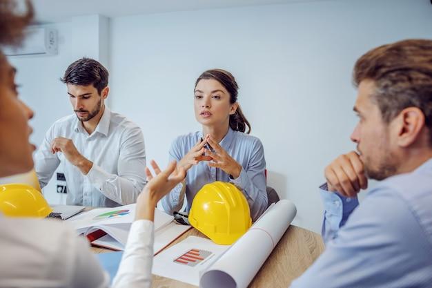 会議室の机に座って会議をしている建築家の多民族グループ。彼らは新しいプロジェクトについて話し合っています。